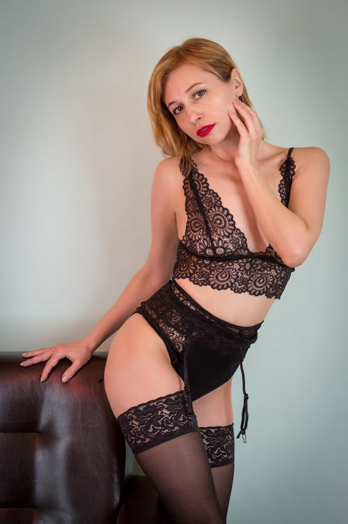 Seductive young female wearing black underwear and stockings standing near leather sofa and touching neck tenderly while looking at camera alluringly