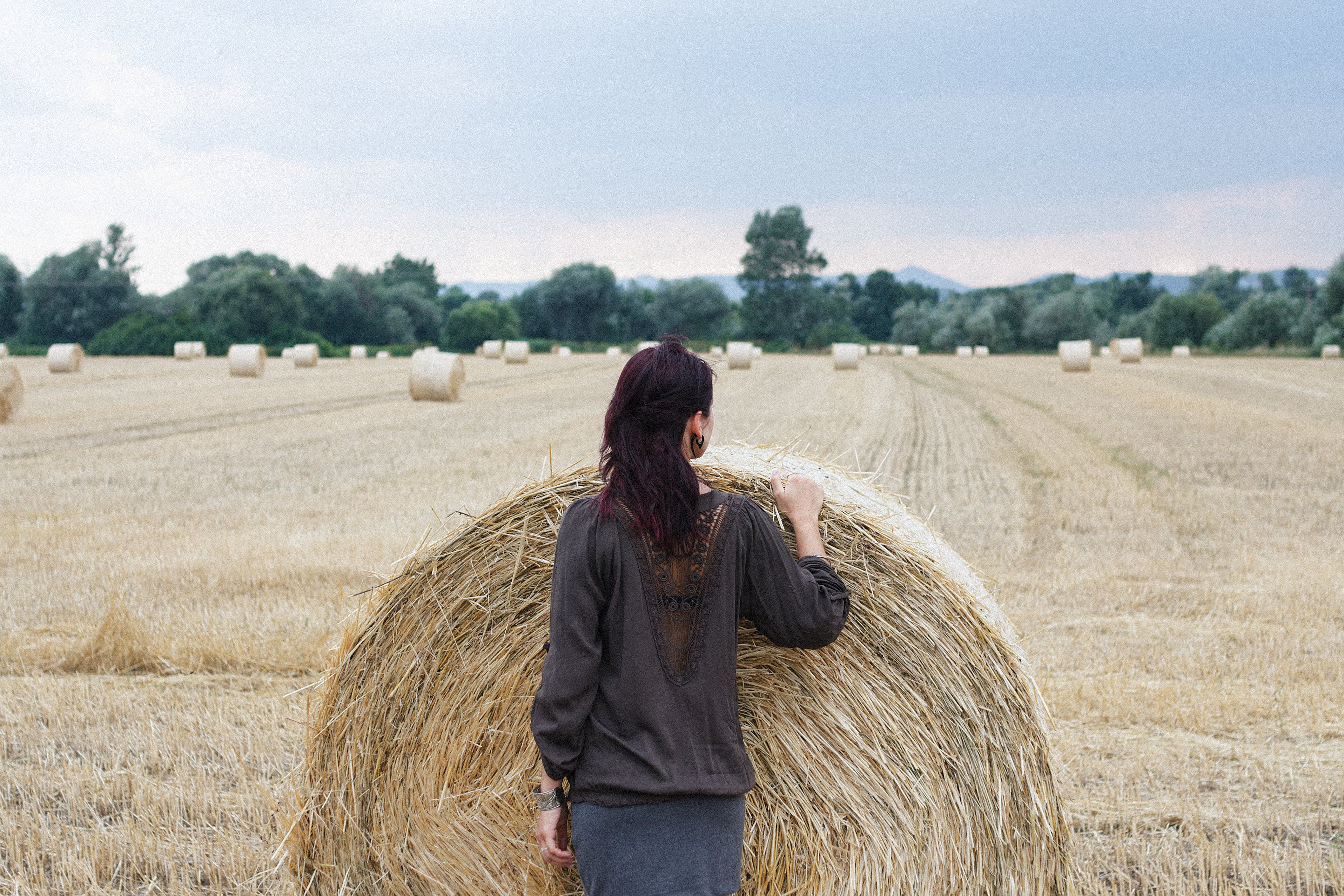 Woman Standing in Front of Hay