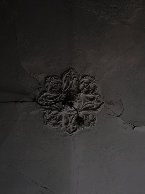 From below of ceiling with old lamp and broken stucco in forgotten shabby dark room
