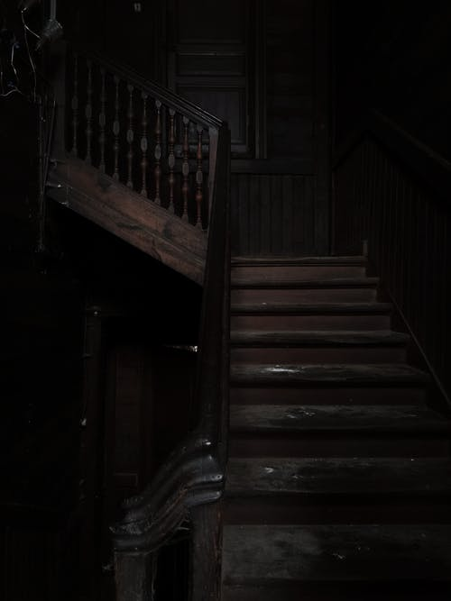 Dark gloomy interior of house with timber shabby stairs in abandoned gray building