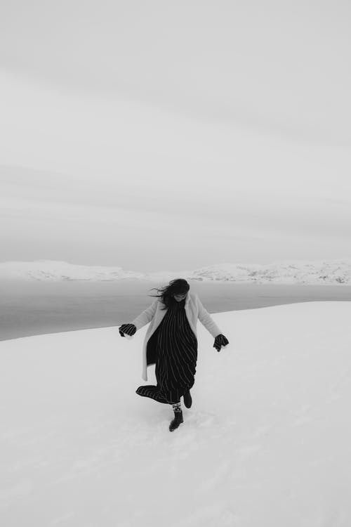 A Grayscale of a Woman Wearing a Fur Coat Walking on Snow