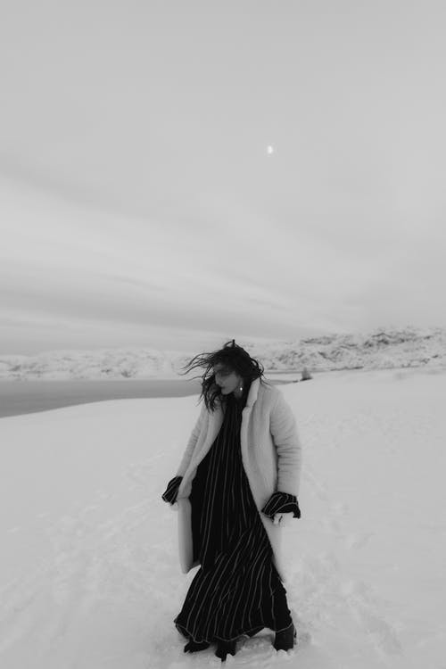 A Grayscale of a Woman Wearing a Fur Coat