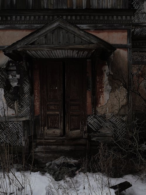 Exterior of aged abandoned house with damaged walls and old timber weather door