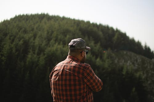 Man in Red and Black Plaid Dress Shirt Wearing Gray Cap Standing in Front of Green