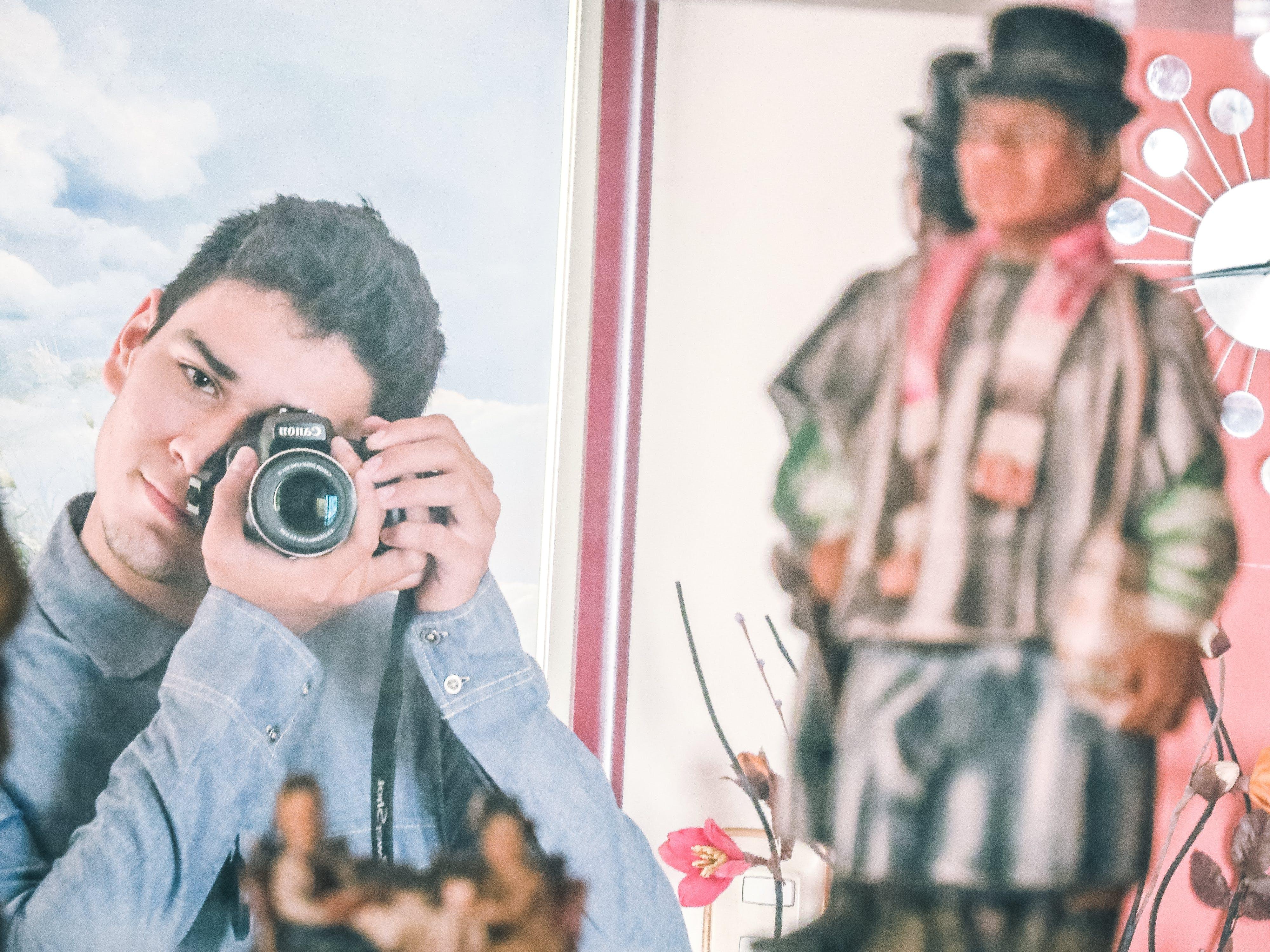 Man in Blue Denim Jacket Using Black Dslr Camera