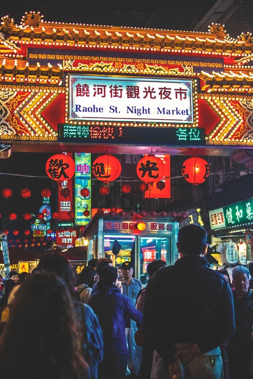 View of Raohe St. Night Market Arch With Kanji Texts and Group of People