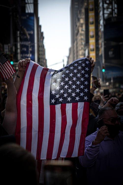 Základová fotografie zdarma na téma americká vlajka, držení, osoba