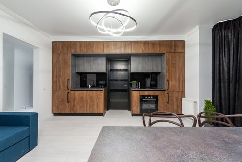 Creative design of kitchen with cupboards and built in oven against table and sofa in house with geometric lamp
