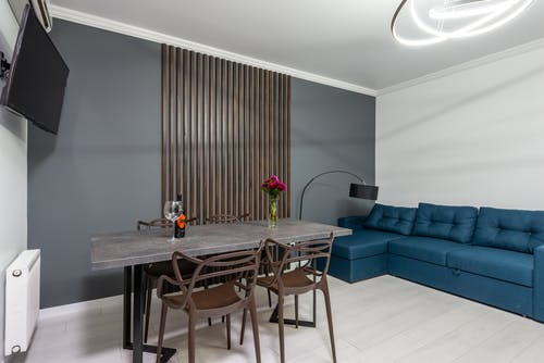 Modern room interior with table and armchairs between TV and couch at home with shiny lamp