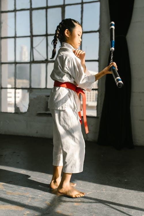 Girl in Taekwondo Uniform Using Karate Sticks