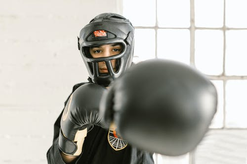 Person Wearing a Head Guard and Black Gloves