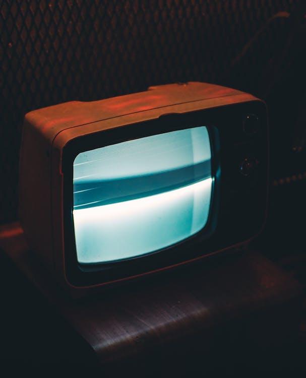 灰色の画面を表示している黒いブラウン管テレビ