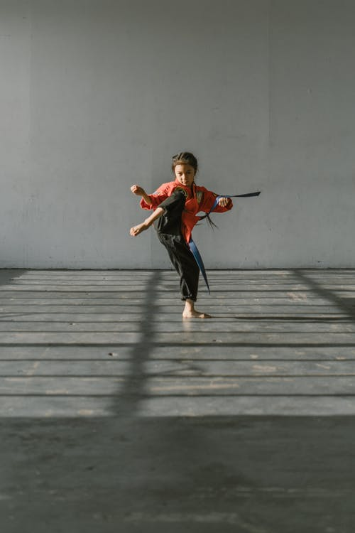 Boy in Red T-shirt and Black Pants Jumping on Gray Wooden Floor