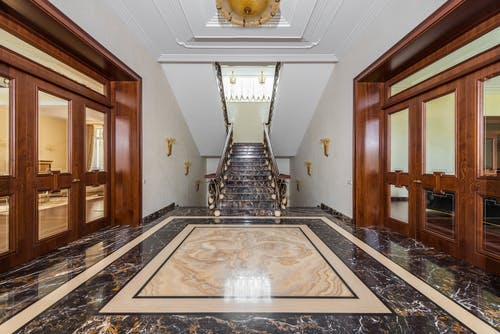 Interior of spacious corridor with marble floor and stairway in luxury apartment in daylight