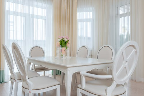 Interior of light flat with white wooden table with vase of flowers and candles near chairs next to windows with curtains in daylight