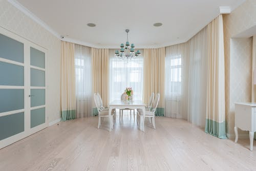 Dining table with chairs in room near windows with curtains