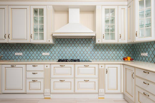 Interior of light modern kitchen with wooden white cabinets and blue tile backsplash with classic hood
