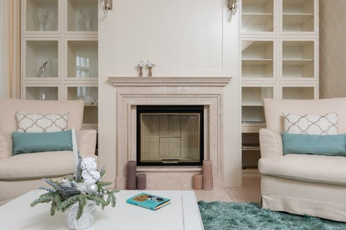 Interior of modern living room with armchairs on carpet near table next to marble pink fireplace