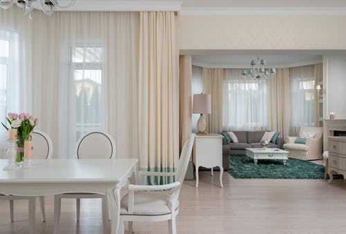 Dining table with chairs near windows with curtains and couches
