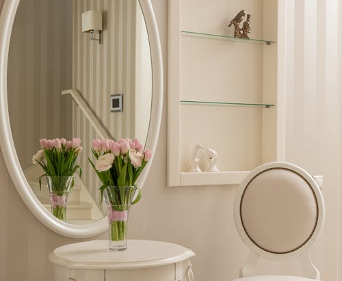Fresh aromatic bouquet placed on light table near mirror in stylish room in daytime