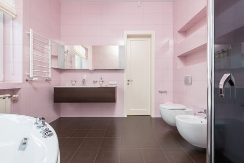 Interior of modern bathroom in pink and brown colors with white bathtub and glass shower cabin and mirror hanging on wall