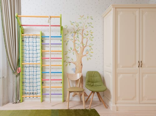 White wall with tree image in light bedroom for kid with wardrobe and colourful play area
