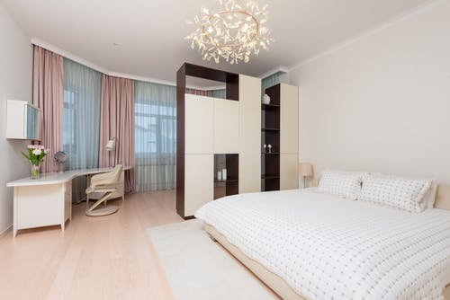 Contemporary interior of light spacious bedroom with bed and wardrobe with shelves and workplace