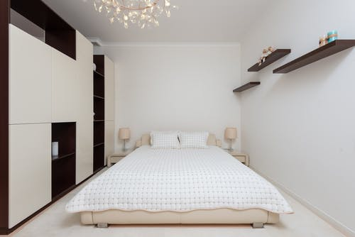 Interior of contemporary large bedroom with black shelves and bed with soft cushions