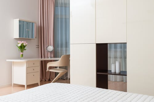 Interior of contemporary spacious apartment with white wardrobe and black shelf near bed