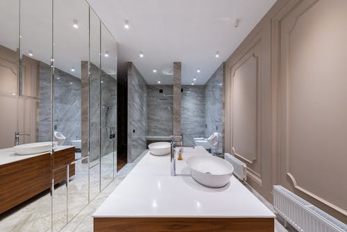 Interior of empty stylish light bathroom with mirrored cabinet placed in modern apartment