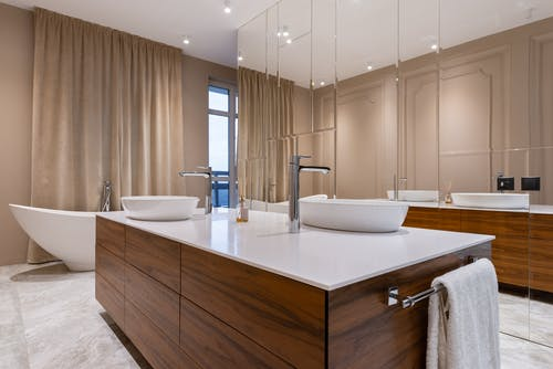 Minimalistic interior of modern bathroom with white sink and bath and mirrored cabinet in apartment in daytime