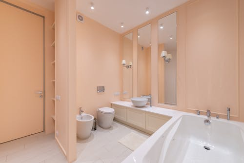 Interior of spacious bathroom with beige walls and clean white bath and sink placed near toilet and bidet