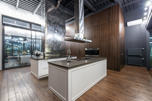 Interior of stylish spacious kitchen zone with stylish furniture placed in modern apartment