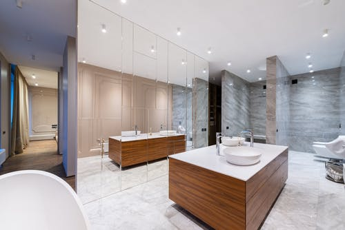 Interior of stylish spacious bathroom with mirrored wall placed in modern luxury apartment