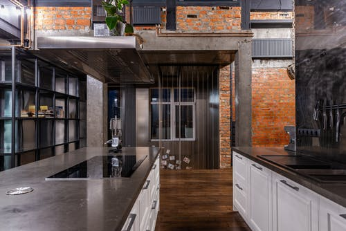 Interior of spacious kitchen area with modern furniture placed in luxury apartment in loft style