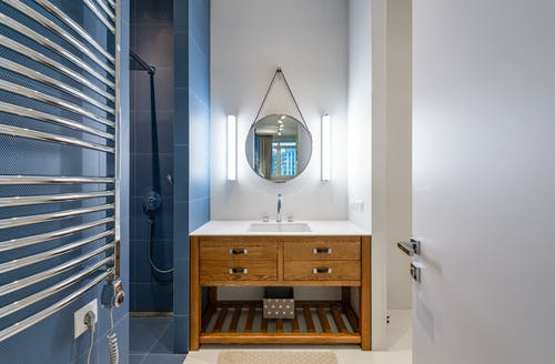 Clean sink with placed under round mirror near shower with blue tile in bathroom in modern apartment
