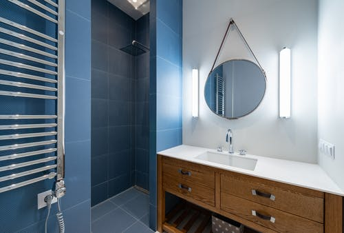 Interior of stylish bathroom with blue tile in shower and round mirror hanging on wall above sink