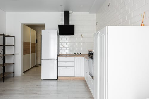 Contemporary kitchen with refrigerator and hood against decorative white brick wall in house with empty shelves on parquet
