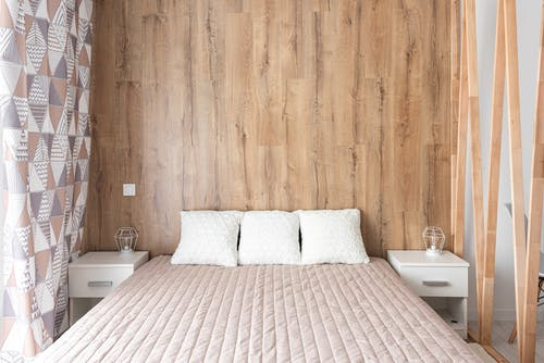 Contemporary bedroom interior with bed against wooden wall