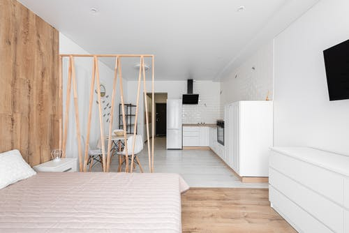 Creative design of bedroom with bed and TV against refrigerator with cabinets on floor in light house