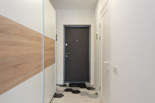 Entrance door between white brick wall against narrow passage with closet and rug with hexagonal ornament in house