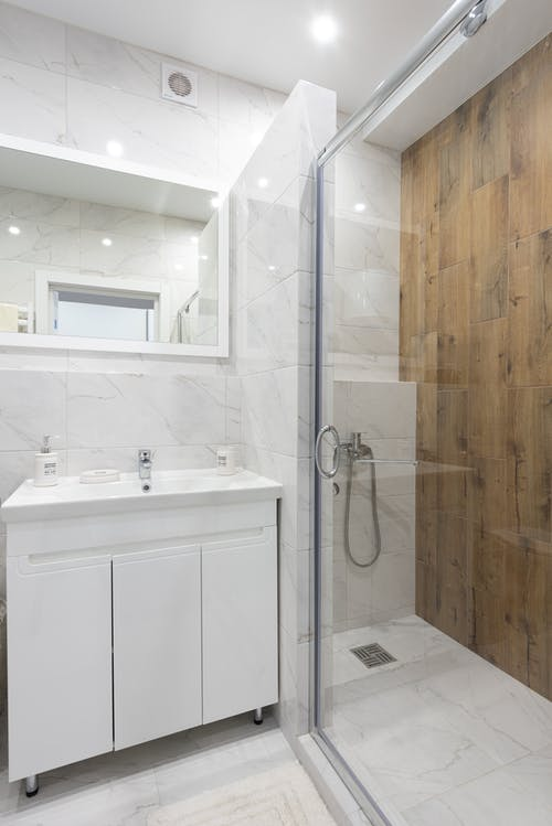 Creative design of bathroom with washbasin between cabinet and mirror against glass door of shower room in light house