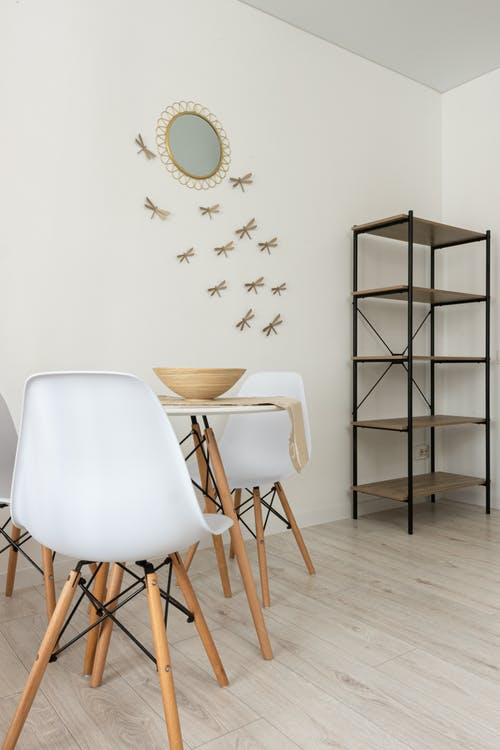 Table with bowl between chairs and shelves against wall with mirror and decorative dragonflies at home