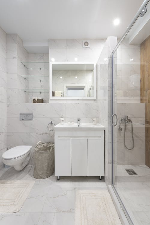 Contemporary bathroom with toilet bowl against cloth basket and washstand under mirror with shiny lights in house