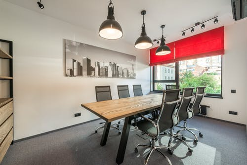 Wooden table with comfortable chairs in modern spacious conference hall with creative lamps and jalousie on windows