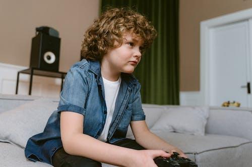 Boy in Blue Denim Button Up Shirt Sitting on Bed