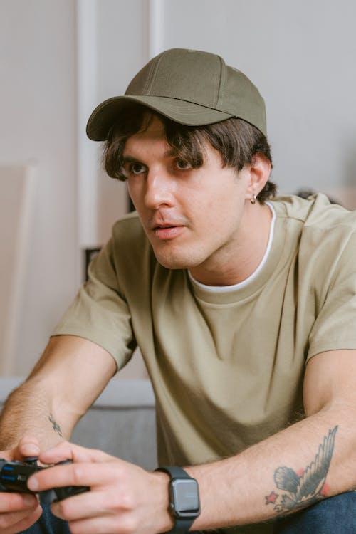 Man in Brown Crew Neck T-shirt Wearing Black Cap