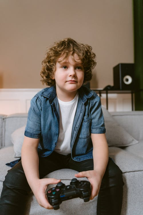 Boy in Blue Denim Button Up Shirt Sitting on Gray Couch
