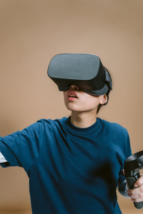 A Person in Blue Shirt Playing a Virtual Reality Video Game