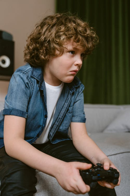 Close-Up Shot of a Boy Holding a Video Game Controller while Sitting on the Sofa